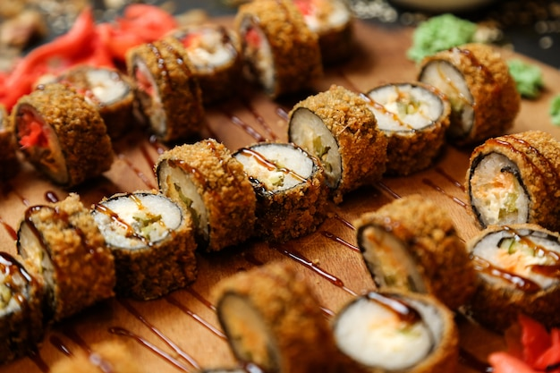 Vista lateral rolos de sushi frito em uma bandeja com gengibre e wasabi
