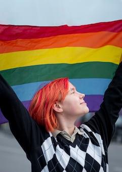 Vista lateral, ruiva, pessoa não binária segurando uma bandeira lgbt