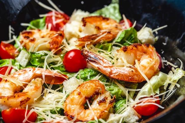 Vista lateral salada caesar com camarão grelhado alface tomate cereja e parmesão em um prato