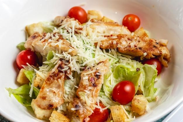Vista lateral salada caesar com tomate cereja parmesão frango grelhado e alface em um prato