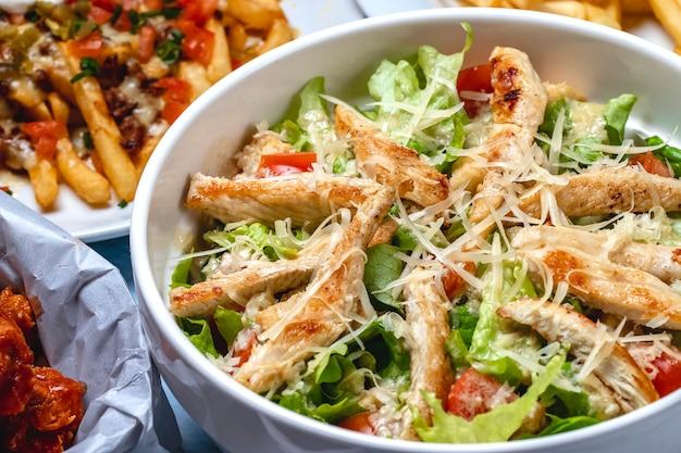 Vista lateral salada caesar frango grelhado tomate fresco alface e queijo parmesão