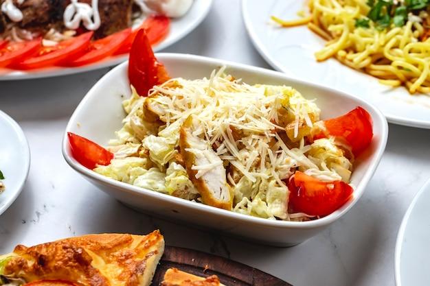 Vista lateral salada caesar grelhado frango filé tomate alface e parmesão em uma placa