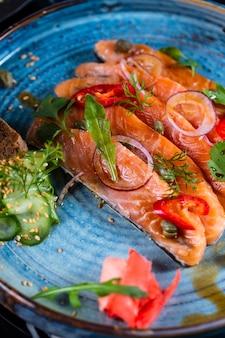 Vista lateral salmão defumado com cebola pepino e ervas num prato azul