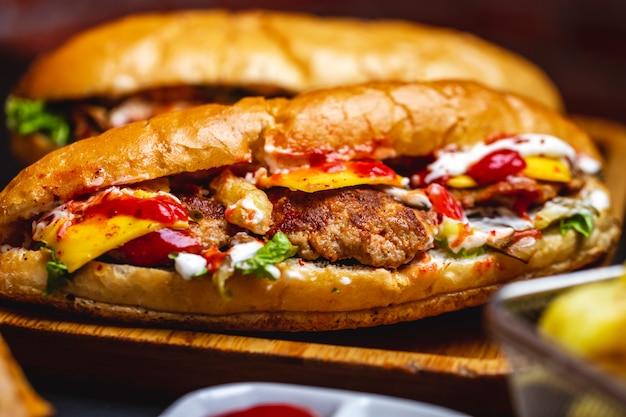 Vista lateral, sanduíche, pão branco, com, carne grelhada, costeleta, queijo, alface, batatas fritas maionese, e, ketchup, ligado, um, boardjpg