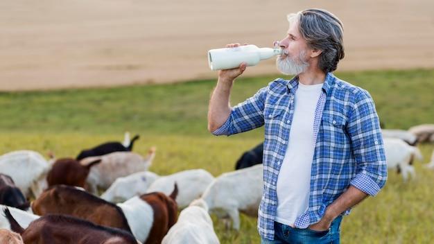 Vista lateral sênior bebendo leite de cabra