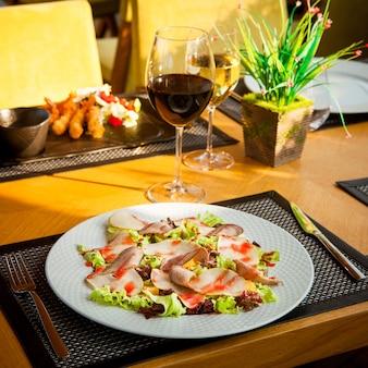 Vista lateral servida camarão de mesa em massa com alface, tomate e molho em um prato preto, prato com salada, copos de vinho