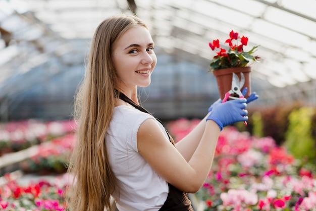 Vista lateral sorridente feminino segurando o vaso de flores