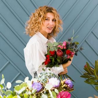 Vista lateral sorridente florista segurando um buquê de flores