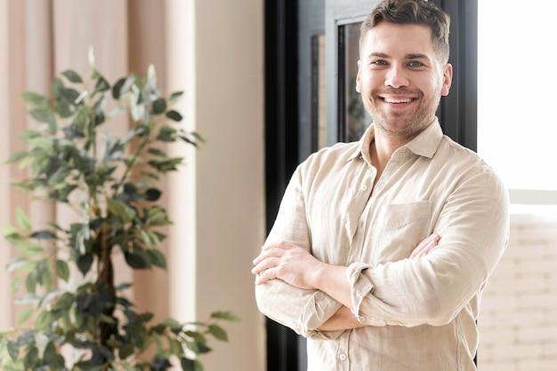 Vista lateral sorridente homem com braços cruzados