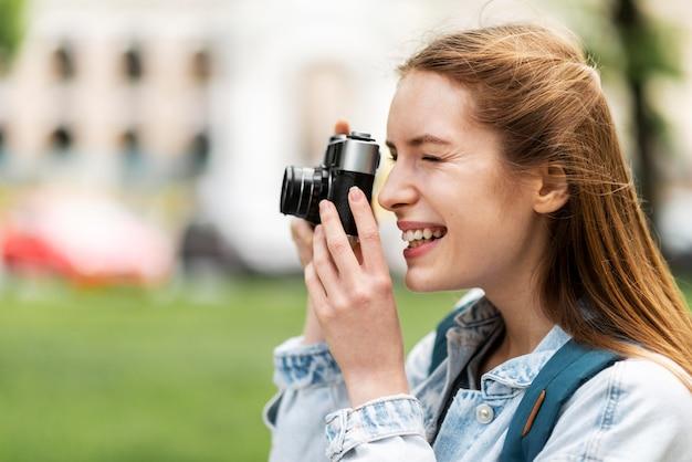Vista lateral sorridente menina tirando uma foto