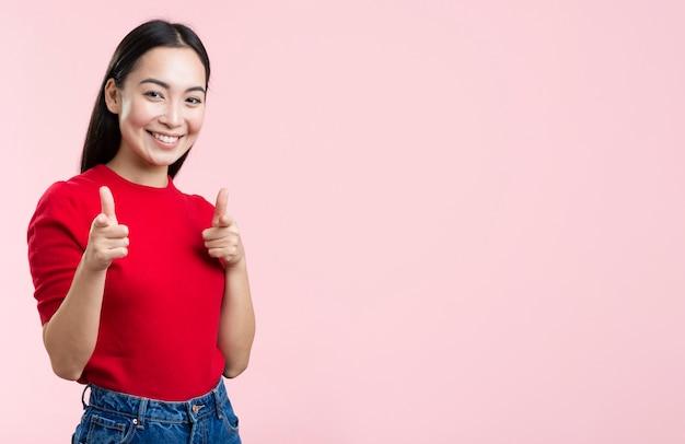 Vista lateral sorridente mulher apontando para a câmera