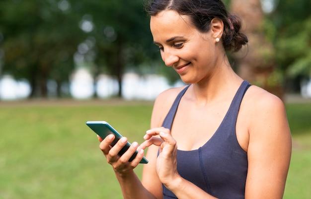 Vista lateral sorridente mulher com smartphone