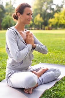 Vista lateral sorridente mulher meditando pose