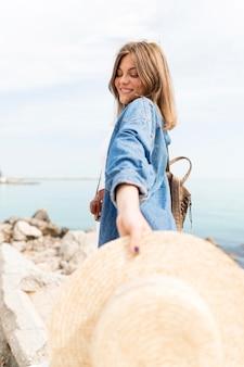 Vista lateral sorridente mulher posando com chapéu