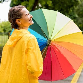 Vista lateral sorridente mulher segurando um guarda-chuva colorido