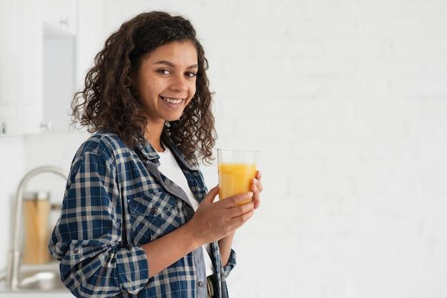 Vista lateral, sorrindo, mulher bebendo suco laranja