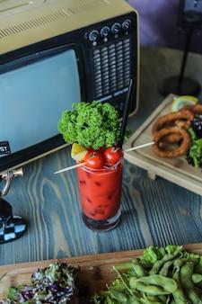 Vista lateral suco de tomate com tomate limão e ervas em um copo