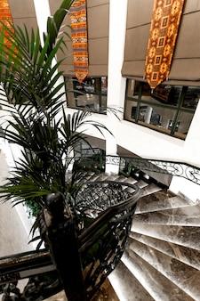 Vista lateral superior das escadas do restaurante de mármore preto e janelas longas com persianas de tecido
