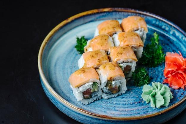 Vista lateral sushi rolos filadélfia com abacate e wasabi em um prato