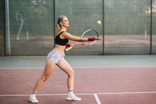 Vista lateral, tenista, recebendo bola
