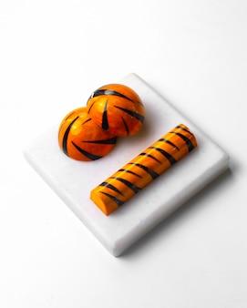 Vista lateral tigre cor doces de chocolate no carrinho branco
