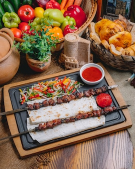 Vista lateral tike kebab em espetos no pão pita com salada de legumes e ketchup