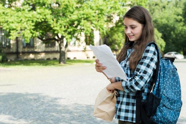 Vista lateral, tiro médio, de, highschool, menina, notas leitura