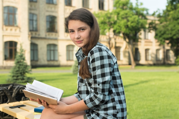 Vista lateral, tiro médio, de, menina adolescente, segurando, livro aberto