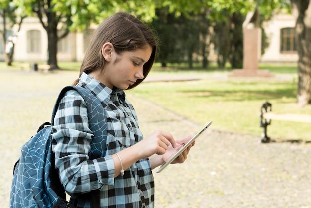 Vista lateral, tiro médio, de, menina escola, usando, tabuleta