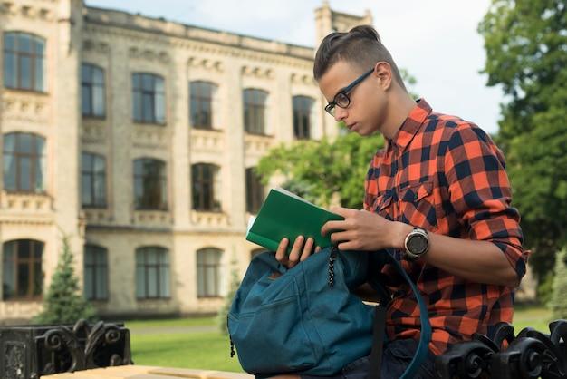 Vista lateral, tiro médio, menino adolescente, lendo um livro