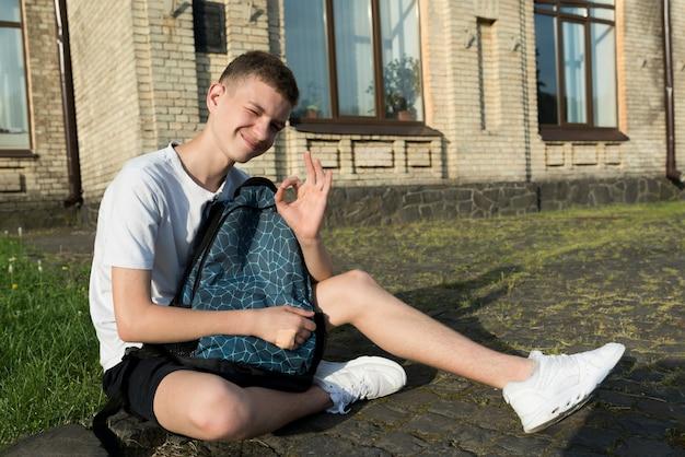 Vista lateral, tiro, sentando, menino adolescente, segurando, um, mochila