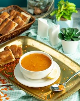 Vista lateral tradicional sopa de lentilha azerbaijana com pão tandoor em uma bandeja