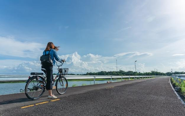 Vista lateral traseira da mulher ocasional que biking no cais que olha o lago natural no dique com o punho no ar.