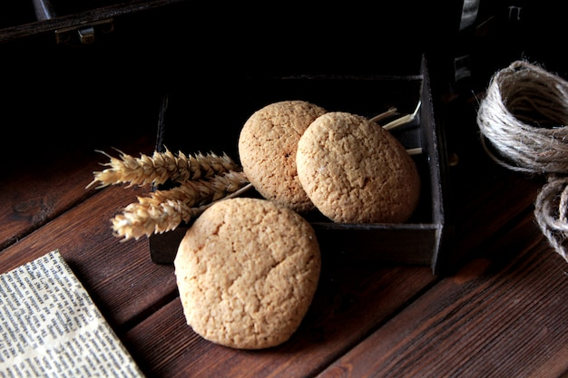Vista lateral três biscoitos de aveia com linha e jornal