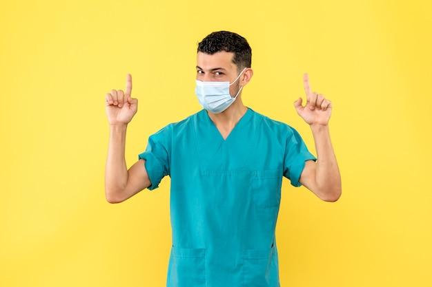 Vista lateral um médico um médico com a máscara e uniforme médico aponta para cima