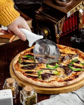 Vista lateral, uma menina corta pizza de carne com pimentão e molho de churrasco em uma bandeja