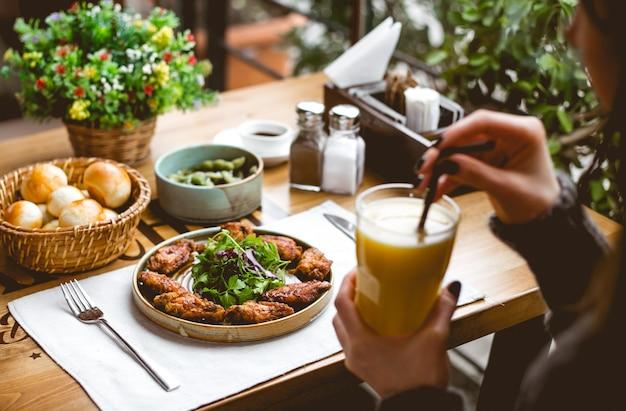 Vista lateral, uma mulher bebe suco de laranja com frango frito em massa com ervas