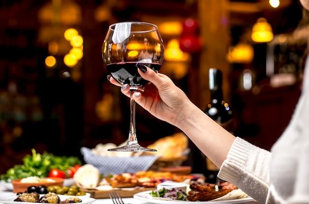 Vista lateral, uma mulher bebe um copo de vinho tinto