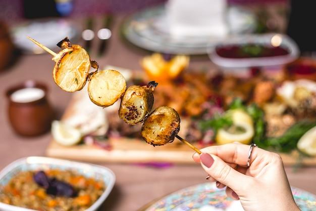 Vista lateral, uma mulher come kebab de batata no espeto