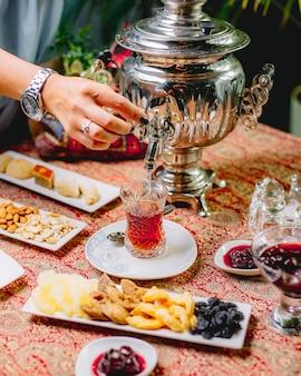 Vista lateral, uma mulher derrama chá de um bule de samovar em um copo de armuda em um pires