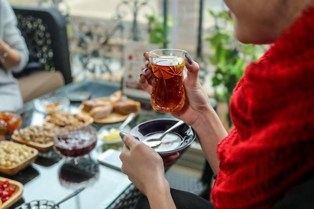 Vista lateral, uma mulher está bebendo chá em um copo de armudu com doces em cima da mesa