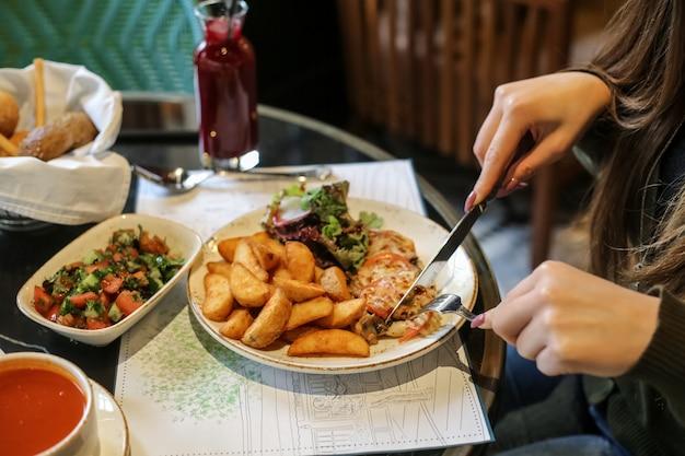 Vista lateral, uma mulher está comendo frango monástico com batatas fritas e salada de legumes com suco em cima da mesa