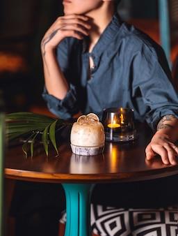 Vista lateral, uma mulher se senta em uma mesa com um cocktail e uma vela acesa
