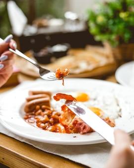Vista lateral, uma mulher tem café da manhã ovos fritos com salsichas feijão e bacon em um prato