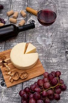 Vista lateral vinho com uva e queijo e na vertical de madeira branca