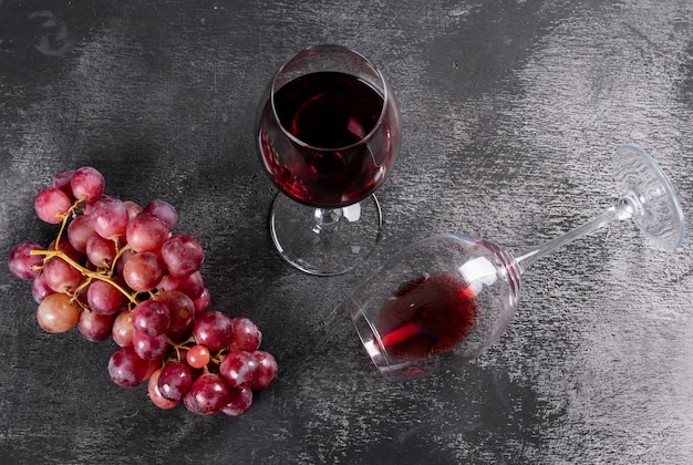 Vista lateral vinho tinto com uva na pedra preta horizontal