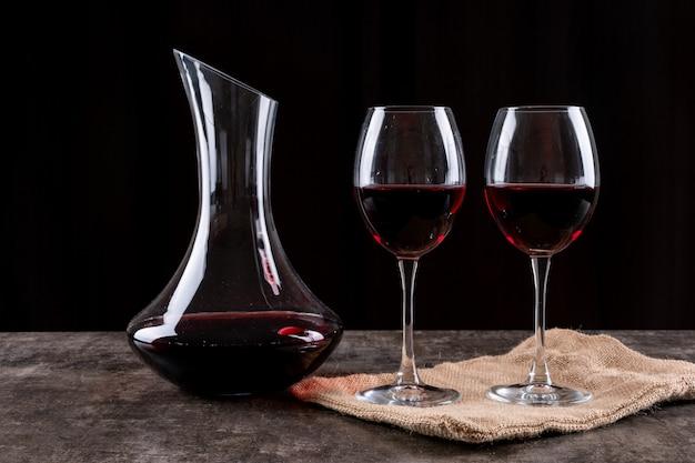 Vista lateral vinho tinto em copos e pano de linho no escuro horizontal