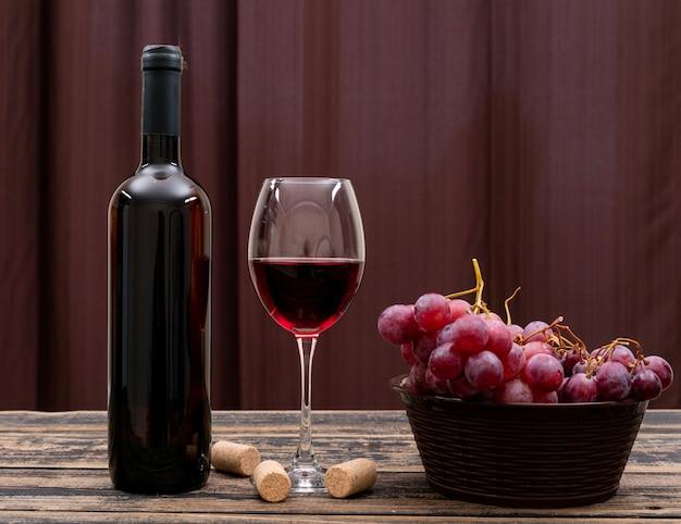 Vista lateral vinho tinto em garrafa, copo e uva na mesa escura e horizontal