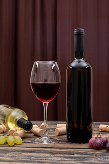 Vista lateral vinho tinto em garrafa, copo e uva na mesa escura e vertical
