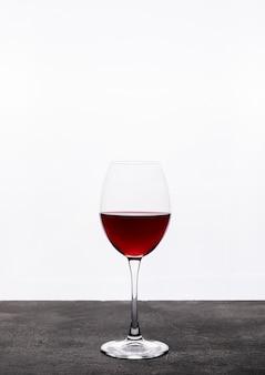 Vista lateral vinho tinto em vidro na vertical branca